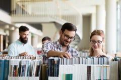 Jeunes étudiants heureux étudiant avec des livres dans la bibliothèque Photos libres de droits
