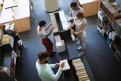 Jeunes étudiants heureux étudiant avec des livres dans la bibliothèque Photographie stock