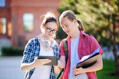 Jeunes étudiants heureux avec des livres et notes dans le campus universitaire Photographie stock libre de droits