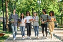Jeunes étudiants heureux marchant tout en parlant Regard de côté Images libres de droits