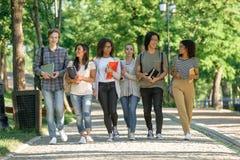 Jeunes étudiants heureux marchant tout en parlant Regard de côté Image libre de droits