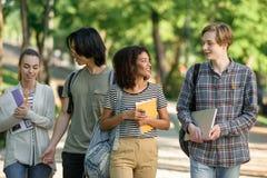 Jeunes étudiants heureux marchant tout en parlant Regard de côté Photographie stock