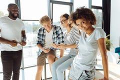 Jeunes étudiants internationaux positifs se reposant ensemble Photos stock