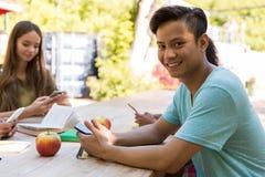 Jeunes étudiants multi-ethniques de sourire d'amis à l'aide des téléphones portables Images libres de droits