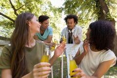 Jeunes étudiants multi-ethniques gais d'amis buvant dehors du jus Images stock