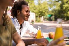 Jeunes étudiants multi-ethniques gais d'amis buvant dehors le juicee Photos stock