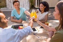 Jeunes étudiants multi-ethniques heureux d'amis buvant dehors du jus Image libre de droits