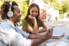 Jeunes étudiants multi-ethniques heureux d'amis parlant les uns avec les autres Images stock
