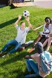 Jeunes étudiants multi-ethniques jouant avec du ballon de football tout en étudiant en parc Photos libres de droits