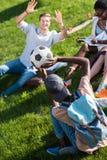 Jeunes étudiants multi-ethniques jouant avec du ballon de football tout en étudiant en parc Images libres de droits