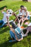 Jeunes étudiants multi-ethniques jouant avec du ballon de football tout en étudiant en parc Image stock