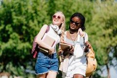 Jeunes étudiants multi-ethniques souriant et parlant tout en marchant en parc Image libre de droits