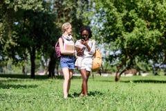 Jeunes étudiants multi-ethniques souriant et parlant tout en marchant en parc Photos libres de droits