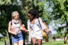 Jeunes étudiants multi-ethniques souriant et parlant tout en marchant en parc Photo libre de droits