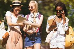 Jeunes étudiants multi-ethniques tenant des livres et des dispositifs numériques tout en parlant et marchant en parc Photographie stock libre de droits