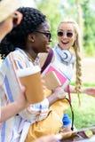 Jeunes étudiants multi-ethniques tenant les livres et la tasse de papier tout en parlant en parc Photo stock