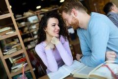 Jeunes étudiants passant le temps dans des livres de lecture de café Images stock