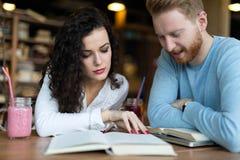 Jeunes étudiants passant le temps dans des livres de lecture de café Photos libres de droits