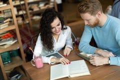Jeunes étudiants passant le temps dans des livres de lecture de café Photographie stock