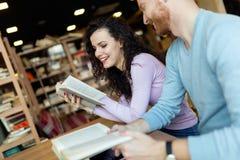 Jeunes étudiants passant le temps dans des livres de lecture de café Photos stock