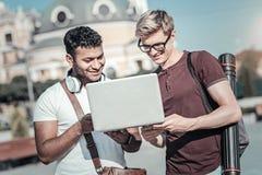Jeunes étudiants positifs à l'aide d'un ordinateur portable Photographie stock