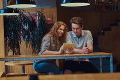 Jeunes étudiants réfléchis de couples à l'aide d'un comprimé numérique tout en se reposant à la table dans la cantine d'universit Image libre de droits
