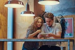 Jeunes étudiants réfléchis de couples à l'aide d'un comprimé numérique tout en se reposant à la table dans la cantine d'universit Photographie stock libre de droits