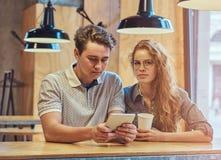 Jeunes étudiants réfléchis de couples à l'aide d'un comprimé numérique tout en se reposant à la table dans la cantine d'universit Image stock