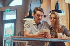 Jeunes étudiants réfléchis de couples à l'aide d'un comprimé numérique tout en se reposant à la table dans la cantine d'universit Photo libre de droits