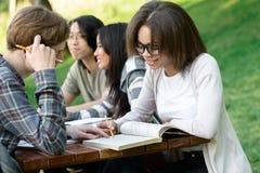 Jeunes étudiants s'asseyant et étudiant dehors tout en parlant Photo libre de droits