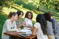 Jeunes étudiants s'asseyant et étudiant dehors tout en parlant Images stock