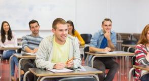 Jeunes étudiants souriant dans la salle de classe Images stock