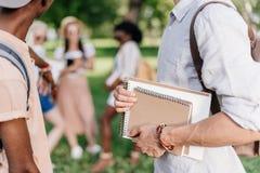 Jeunes étudiants tenant des carnets tout en se tenant en parc Photographie stock