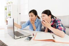 Jeunes étudiants universitaires féminins à l'aide de l'ordinateur portable mobile Photos stock