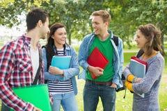 Jeunes étudiants universitaires gais en parc Photo stock