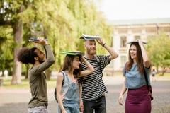 Jeunes étudiants universitaires marchant avec des livres sur leurs têtes Image libre de droits