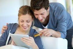 Jeunes achats de couples sur l'Internet Photos stock