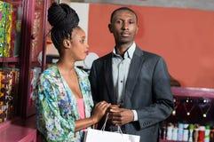 Jeunes achats de sourire de couples photos stock