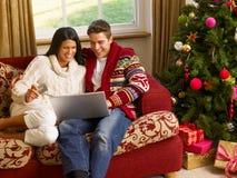 Jeunes achats hispaniques de Noël de couples en ligne Photos libres de droits