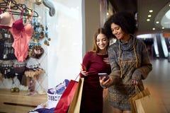 Jeunes achats multi-ethniques heureux de femme du métis deux pour la lingerie près de la fenêtre de magasin de boutique d'habille image libre de droits
