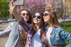 Jeunes adolescentes heureuses faisant le selfie et ayant l'amusement en parc d'été Photo stock