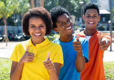 Jeunes adultes d'afro-américain dans une rangée montrant des pouces  Image libre de droits