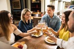 Jeunes adultes faisant un pain grillé avec de la bière Image stock