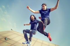 Jeunes adultes heureux sautant sur une terrasse Photos libres de droits