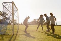 Jeunes adultes jouant le football en parc un dans le but, vue de côté Photographie stock