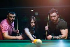 Jeunes adultes jouant le jeu de billard dans le club Photographie stock libre de droits