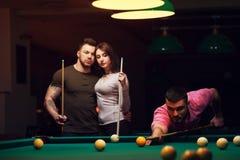 Jeunes adultes jouant le jeu de billard dans le club foncé Photos libres de droits