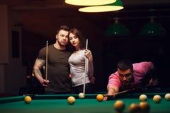 Jeunes adultes jouant le jeu de billard dans le club foncé Photographie stock libre de droits