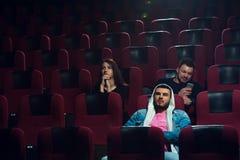 Jeunes adultes observant le film ennuyeux dans la salle de cinéma Image stock
