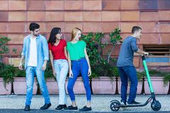 Jeunes adultes regardant à un conducteur électrique de scooter photos libres de droits